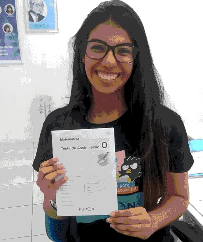 Menina feliz sentada na cadeira, vestindo uma camisa preta, usando um óculos e segurando seu teste de conclusão.